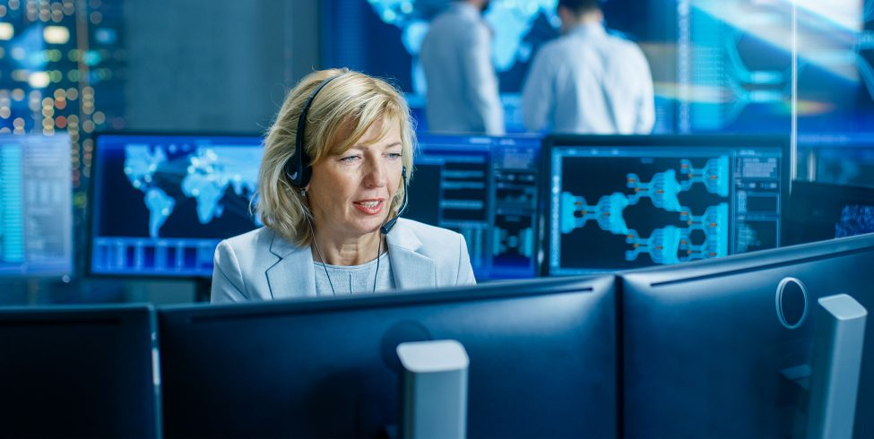 Sales woman with headset in front of computer monitors